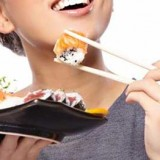 woman-in-gray-eating-sushi-with-chopsticks